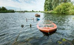 Sunken orange colored row boat Stock Image