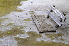 Sunken park bench in deep mud and water Stock Photography