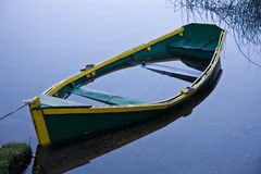 Sunken row boat. Yellow edged rowing boat sunk in blue water Royalty Free Stock Photography