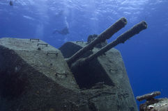 Sunken warship. A diver overlooks the rusting guns on the wreck of the 'Capt. Keith Tibbetts' off of Cayman Brac. This vessel is the only Russian warship in the Stock Photos