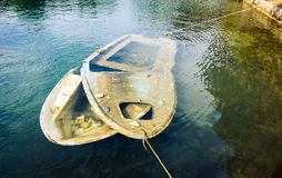 Sunken wooden boat in sea or lake tied to shore. Small plastic boat with broken top is submerged int he sea while still tied to shore and pier with ropes Royalty Free Stock Photography