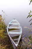 Sunken wooden boat with water stand on river shore. Sunken wooden boat filled with water stand on foggy river coast shore. Romantic transport Stock Images