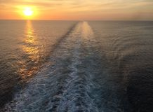 Sunkissed ocean. Ocean sunset, clouds and ship wake stock photos