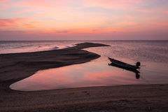 Sunless. Sunset with long tailed boat cast anchor Stock Image
