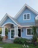 sunlght的明亮的蓝色房子与五颜六色的鸦片和一些grac 免版税库存图片
