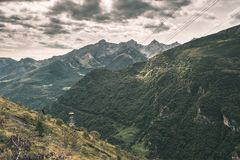 Sunlight on alpine valley with glowing mountain peaks and scenic clouds. Italian French Alps, summer travel destination, toned ima Royalty Free Stock Images