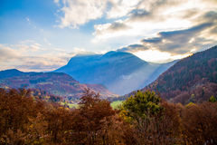 Sunlight breaking through the clouds over a mountain. In autumn Royalty Free Stock Images
