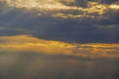Sunlight breaks through the storm clouds. Cloudy sky at sunset royalty free stock photo