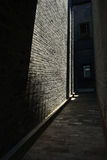 Sunlight on building in alley. Sunlight on the wall of an old-fashioned building in a dark narrow alley,Chengdu,China Stock Photo
