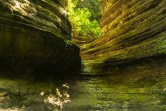Sunlight into the canyon. Sunlight shining into Aurora Canyon as water softly flows through the canyon.  Starved Rock State Park, Illinois Stock Photo