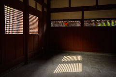 Sunlight cast on floor through latticed windows of ancient Chine Stock Images