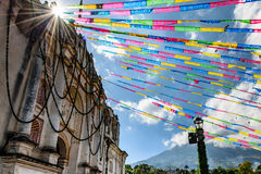 Sunlight on church & volcano near Antigua, Guatemala. One of oldest Catholic churches in Guatemala in festive colors with Agua volcano behind. In small village stock photo