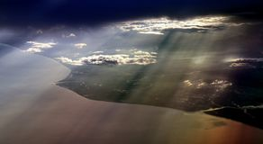 Sunlight through clouds. Rays of sunlight streaming through clouds.  Aerial perspective over coastline Stock Image