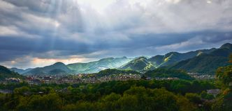 Sunlight through the clouds illuminated mountains. ,the houses are surrounded by mountains stock image
