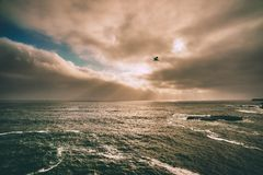 Sunlight through clouds over waves Stock Photography