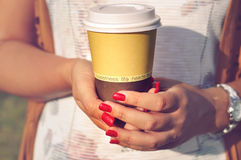 Sunlight on the coffee to go and woman hands with red nails. Royalty Free Stock Photo