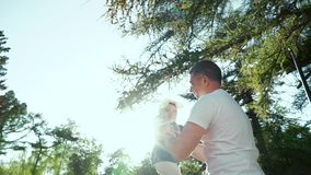 Sunlight on father throwing up his toddler daughter in summer garden. With lens flare effect. man spendiing leisure time with adorable baby girl outdoors stock footage