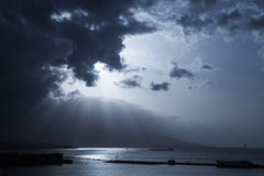 Sunlight goes through dark stormy clouds Stock Images