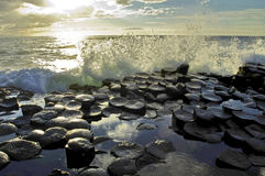 Sunlight highlighting waves crashing onto the hexagonal Basalt slabs of Giants Causeway Royalty Free Stock Photo