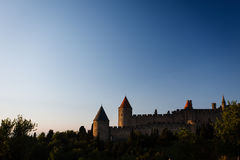Sunlight highlights the castle turrets walled city. Sunlight highlights the castle turrets as the day ends in the medieval walled city of Carcassonne France Royalty Free Stock Photography