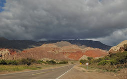 Road leading to vibrant colored rocks under a dramatic sky. El Cafayate, driving to Salta, spectacular landscapes. Colorful rock formations, harsh nature. The stock photography