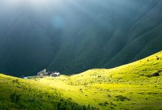 House in the sunlight, in a green mountain valley Stock Photos