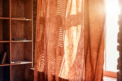 Sunlight from outside window streams into a room through curtains. Sunlight from outside window streams into a room through curtains Stock Photos