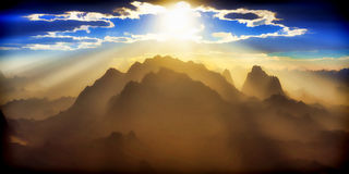 Sunlight over badlands. Rays of sunshine streaming down over inhospitable mountains Stock Image