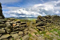 Sunlight over the Ullswater fells. Dry stone wall on the summit of Thornthwaite Crag Stock Photos
