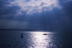 Sunlight over water. Sun rays streaking through the clouds over water Stock Photo