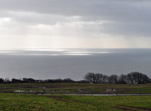 Sunlight on parts of the sea. Sunlight breaks through cloud and lights up the sea Stock Photo