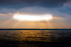 Sunlight passes through the clouds. Horizontally. The sun makes its way from behind the clouds, illuminating the surface of the lake Royalty Free Stock Image