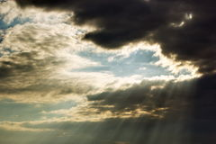 Sunlight penetrating black clouds. Surreal picture with light conquering the dark Royalty Free Stock Photo