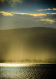 Sunlight through rain by the fjord. Sunlight through rain at sundown by the Mjosa fjord in Norway stock photos