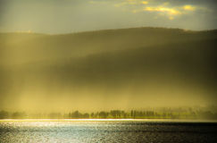 Sunlight through rain by the fjord. Sunlight through rain at sundown by the Mjosa fjord in Norway stock images