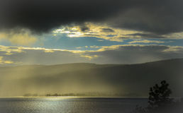 Sunlight through rain by the fjord. Sunlight through rain at sundown by the Mjosa fjord in Norway stock image