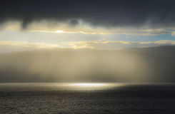 Sunlight through rain by the fjord Royalty Free Stock Images