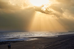 Sunlight rays bursting through the clouds on to the sea below Stock Photos