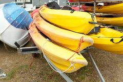 In sunlight, red, yellow and white kayaks placed upside down on metal storage racks. Stocked canoe in the Brest, France 28 May 201. 8 stock photo