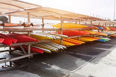 In sunlight, red, yellow and white kayaks placed upside down on metal storage racks. Stocked canoe in the Brest, France 28 May 201. 8 stock photos