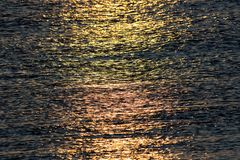 Sunlight reflecting off calm sea water at sunrise. Abstract text Royalty Free Stock Photos