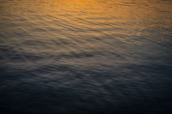 Sunlight reflecting in water. Sunlight reflecting in ripples across the yellow and blue water Stock Photo