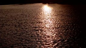 Sunlight reflection in water in the sunset, sea waves with sun setting down.  stock video footage