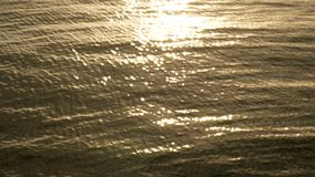 Sunlight reflects sparkling and glitter off of the water surface on a sunset time, abstract blurry background at the seaside. Wonder of nature background with stock footage