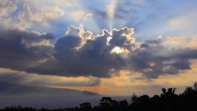 Sunlight shines behind the cloud at dawn with mountain view stock video footage