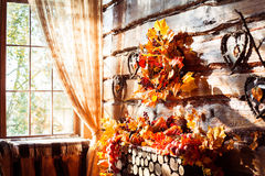 Sunlight shining through a window in a room with wooden walls an. D floor decorated autumn wreath, leaves, wicker hearts and vegetables Royalty Free Stock Photography