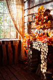 Sunlight shining through a window in a room with wooden walls an. D floor decorated autumn wreath, leaves, wicker hearts and vegetables Royalty Free Stock Image