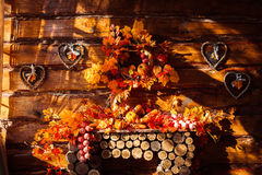 Sunlight shining through a window in a room with wooden walls an. D floor decorated autumn wreath, leaves, wicker hearts and vegetables Stock Image