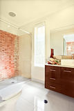 Sunlight spreading inside of a modern bathroom wall and the floor. Luxury bathroom has white floor tiles, exposed to the sunlight. The brown wooden cabinet has stock images