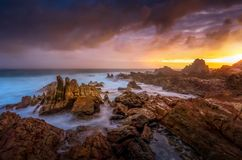Sunlight through storm clouds on a rocky craggy coastal landscape royalty free stock photography